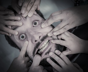 Man's face stretched by people's hands