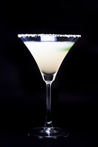 Margarita in glass with lime isolated on black background