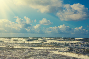 Marine landscape with stormy sea and blue cloudy sky