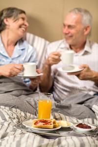 Mature couple enjoying romantic breakfast at hotel room