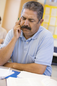 Mature male student frowning in class
