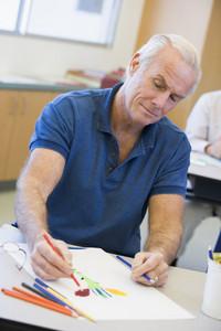 Mature male student in art class