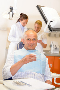 Mature man being treated at dental surgery smiling