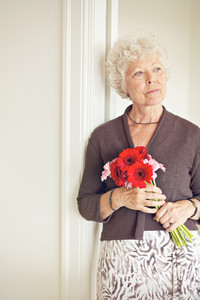 Mature woman holding a bouquet of flowers posing