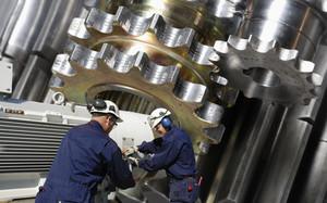 mechanics working on gears and cog machinery