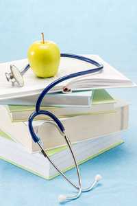 Medical books,apple and stethoscope healthy lifestyle medical research