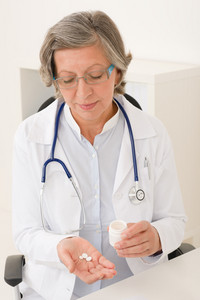 Medical doctor senior female at office holding pills professional portrait