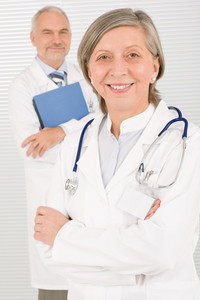 Medical doctor team mature woman and senior man holding folders