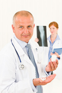 Medical doctor team senior male holding pills young female colleague