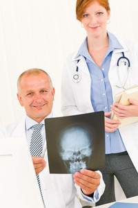 Medical doctor team senior man female colleague hold head x-ray