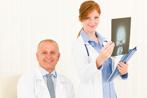 Medical doctor team senior man with female colleague hold x-ray