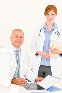 Medical doctor team senior man with female colleague point x-ray