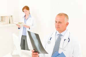Medical doctor team senior man with female nurse look x-ray