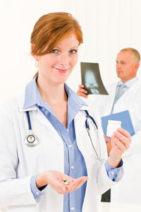 Medical doctor team young woman holding pills male senior colleague