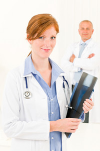 Medical doctor team young woman holding x-ray senior male colleague