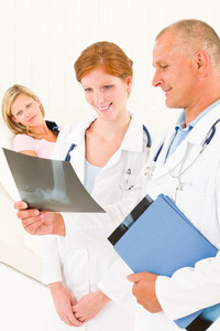 Medical doctors look at x-ray hospital patient in bed broken arm