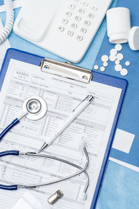 Medical equipment and patient care report on doctor's office desk