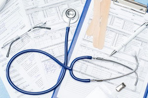 Medical equipment on doctor's office desk stethoscope patient documents
