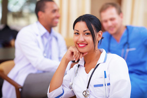 Medical latin doctor woman smiling indoors with her collegues working behind