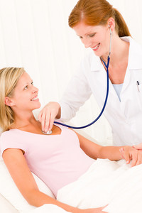 Medical professional doctor stethoscope examine woman patient lying in bed