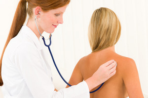 Medical professional doctor with stethoscope examine woman patient naked back
