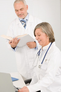 Medical senior doctor female look computer with professional male colleague