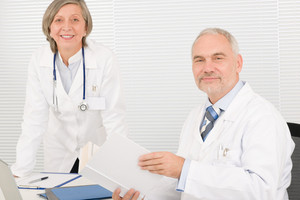 Medical senior doctor male reading book with professional female colleague