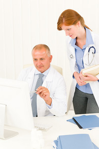 Medical senior doctor male with professional  female colleague point computer