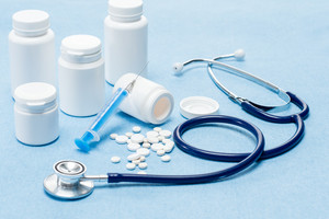 Medical supplies with spilled pills,injection and stethoscope