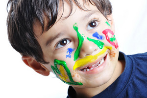 Messy cute kid with colors on his face, funny scene