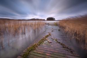 Lake with jetty. long exposure landscape. Autumnal bad weather landscape photographed on polish lake.--