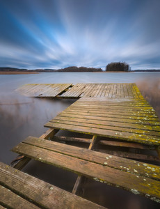 Lake with jetty. long exposure landscape. Autumnal bad weather landscape photographed on polish lake.--