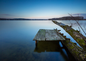 Small pier on lake long exposure photo. Mazury lake district.