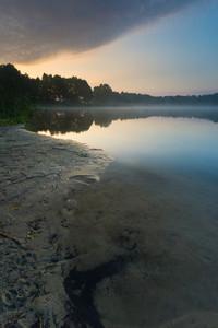 Beautiful sunrise over misty lake. Foggy morning over lake in Mazury lake district