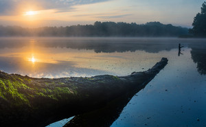 Beautiful sunrise over misty lake. Foggy morning over lake in Mazury lake district