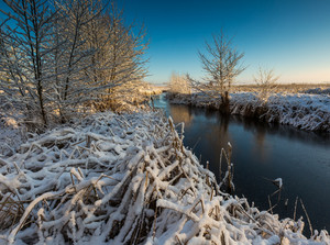 Beautiful winter landscape with frozen river. Good sunny weather winter landscape.