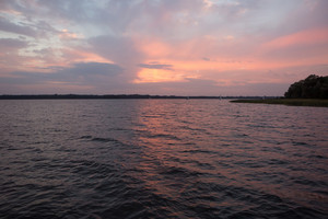 Beautiful lake surface photographed from yacht. Tranquil sunset scene with cloudy sky over lake surface.