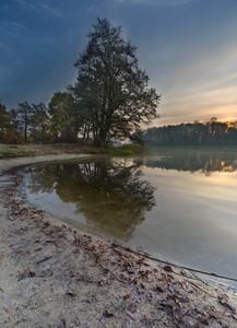 Beautiful sunrise over lake. Tranquil vibrant landscape with polish lake.