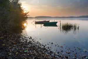 Beautiful lake sunrise with sky reflections in water. Tranquil colorful scene of typical polish lake in Mazury lake district.