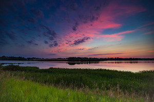 Beautiful colorful sunset over calm lake near city Olsztyn in Poland. Summertime landscape with sunset over lake