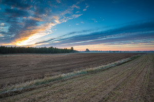 Beautiful landscape with plowed field under sunset or sunrise sky. Agriculture of Poland.