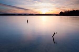 Beautiful long exposure landscape of lake in Mazury lake district (Krzywe lake near Olsztyn).