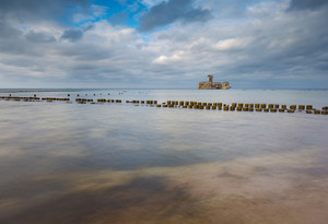 Beautiful view on Baltic sandy coast with old military buildings from world war II and wooden breakwaters. Long exposure photo