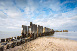 Beautiful view on Baltic sandy coast with old military buildings from world war II and wooden breakwaters. Long exposure photo--