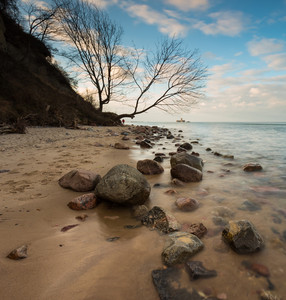 Beautiful rocky sea shore at sunrise or sunset. Long exposure landscape. Baltic sea near Gdynia in Poland.
