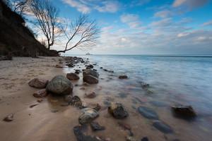 Beautiful rocky sea shore at sunrise or sunset. Long exposure landscape. Baltic sea near Gdynia in Poland.