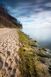Beautiful long exposure landscape of rocky sea shore. Tranquil scene of Baltic sea.