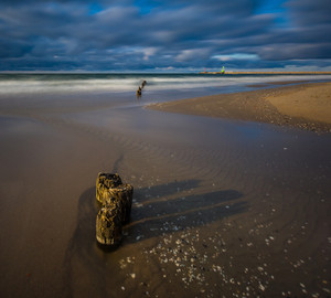 Baltic sea shore with old wooden breakwater palisade. Long exposure photo with dramatic sky