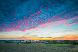 Beautiful and spectacular sunset sky over calm countryside. Polish rural landscape