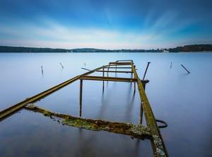 古い破壊されたスチール構造(ボート用のウインドラス)と湖岸の長時間露光風景。オルシティン湖Krzywe